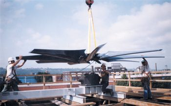 commercial fan being lowered by a crane, technicians guiding it into place