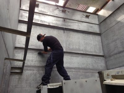 interior of counter flow cooling tower; CTM technician removing caulking from wall