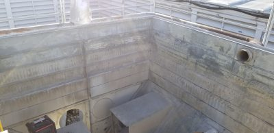 looking down into the interior of an empty recently repaired tower with view of the fan snouts