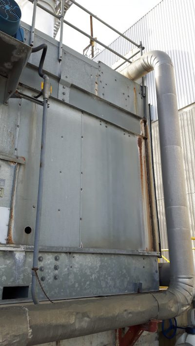 rusting panel of an older package steel tower with dented piping