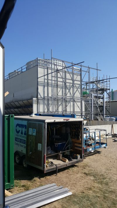 building an additional cell to a field erected tower, metal framing being erected