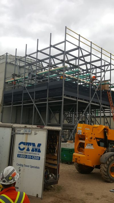 adding an additional cell to a field erected tower, metal framing erected and drift eliminators installed, technicians installing spray system