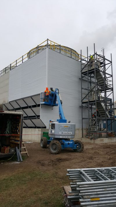 recently rebuilt field erected tower corner view with two technicians in a cherry picker working on the metal paneling of the louvers