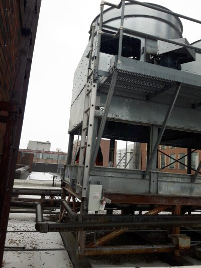 Exterior view of a induced draft counterflow tower with ladder and platform during repair louvers removed