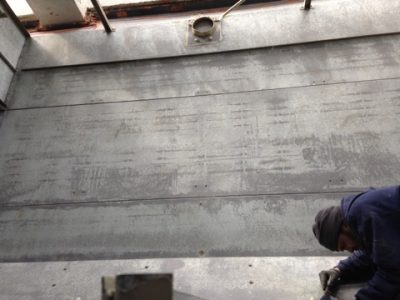 interior of counter flow cooling tower; CTM technician removing caulking from wal
