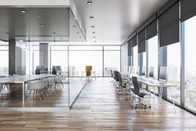 Bright open commercial office space with walls of windows, modern furniture and computers